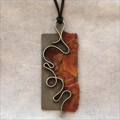 Autumn pendant: Oxidized sterling silver pendant paired with red autumn leaves. Laura Crawford
