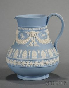 Wedgwood Solid Light Blue Jasper Jug, England, late 19th century, pear-shaped with applied white classical relief of medallions and trophies within floral festoons terminating at ram's heads, all above bands of foliate designs.