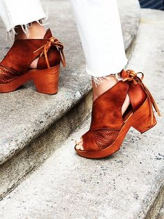 Open toe leather clogs featuring a perforated design on the sides and adjustable ties in back. Grainy wooden heels with padded insoles and treaded rubber soles.