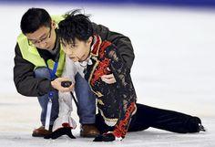 男子フリーの直前練習中に中国選手と激突し、係員に抱えられる羽生結弦選手(8日、上海)=共同