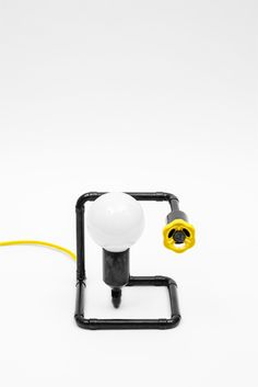 Fun design bedside lamp with creative and functional knob dimmer. Here in black patina metal finish with yellow braided cord and yellow knob.