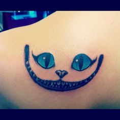 """This was my second tattoo and it's the cheshire cat from Alice in Wonderland. I got it pretty shortly after I got my first one, which is """"We're all mad here"""" on my collarbone. They are just so perfect and fitting together. I'm so happy with the way they both came out.  Done by James Moral at Anchor's Away"""