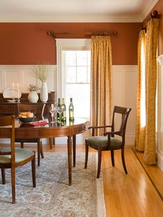 This Traditional Style Dining Room Features White Wainscoting Below Burnt Sienna Walls For A Bright But Earthy Feel Pale Yellow Curtains Continue The Warm
