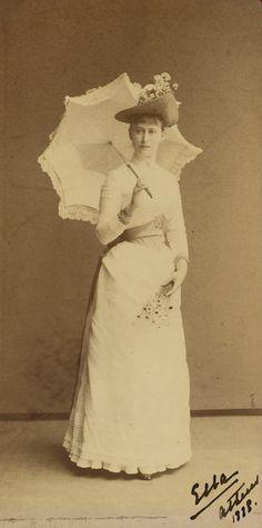 """Grã-duquesa Elisabeth Feodorovna em cerca de 1888. Ela está em pé de frente para a câmera, segurando uma sombrinha de renda aberta atrás dela. Ela está vestindo um longo vestido branco e um chapéu de palha decorado com flores. Ela está segurando um pequeno grupo de margaridas em sua mão esquerda. A fotografia é assinada e datada """"Ella Atenas 1888 'no canto inferior direito."""