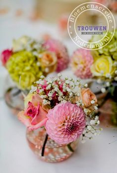 www.trouwenineigentuin.nl Kleine vaasjes met verschillende kleuren bloemen.