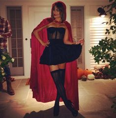 Lea Michele wears a black corset dress with knee high socks and a red cape as Little Red Riding Hood.