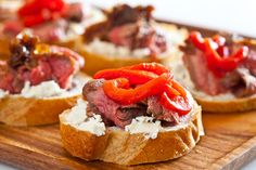 Top crusty bread with flank steak, goat cheese and roasted red peppers to make this appetizer.