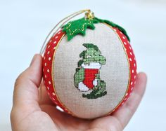 Beautiful baby dragon Christmas ornament! A perfect keepsake for magical time when every detail matters. This bauble is from my series of personalized babys first Christmas ornaments - unique, safe and memorable. ✄✄✄✄✄✄✄✄✄✄✄✄✄✄✄✄✄✄✄✄✄✄✄✄  This babys first Christmas bauble is sewed from the highest quality cotton and linen fabrics with a soft filler inside. One sector is decorated with the miniature hand embroidered Baby Dragon. Another sector can be personalized with babys name and birth…