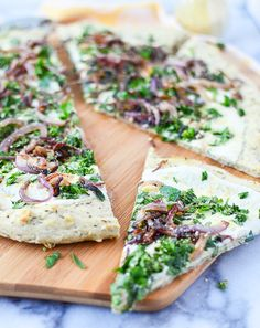 Vegan Garlic Herb White Pizza -- Herb and garlic crust topped with creamy white sauce, caramelized onions, fresh herbs and vegan parm sprinkle.