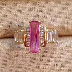 NWOT Sterling Silver, 18kt YG Plated CZ Ring NWOT Sterling Silver, 18kt Yellow Gold Plated and Cubic Zircona Ring.  This ring is so much more brilliant than the photo!  Makes a great middle ring finger.  Set with an elongated pink cubic zirconia in the center with 4 round brilliant CZ's on each side followed by 3 baguette CZ's.  The stones are set low, so it makes it very wearable.  This ring is a nice weight, not a cheap costume ring.  SZ 9. Luxury Boutique Jewelry Rings