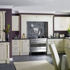This is a unique kitchen! Purple walls and creamy white cabinets