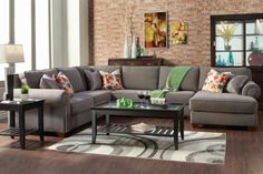 This over-sized, beautiful custom sectional boasts of a plush grey textured fabric (optional), studded arms (optional), a choice of accent pillows. Constructed with a solid wood frame, and seating ranging from soft to medium to firm this sectional makes any living area beautiful and comfy.
