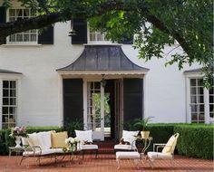 Brick patio & black shutters.