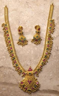 Gold Kundla mala set with matching earrings. The necklace is studded with precious pink and green stones. Jewelry Design Earrings, Gold Earrings Designs, Gold Jewellery Design, Necklace Designs, Beaded Jewelry, Jewellery Box, Jewelry Sets, Sutra, Gold Ring Designs