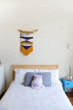House Tour: A Handmade Berkeley Apartment | Apartment Therapy - Handmade macrame fiber art makes this bedroom. DIY art is found throughout this home adding a personal and colorful touch that's easy to do yourself with a kit or on your own.