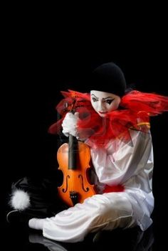 Sad Pierrot sitting on the floow with an old violin Stock Photo