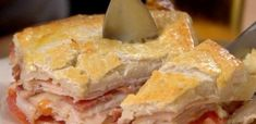 Kentucky Hot Brown Sandwich  – 1 roll refrigerated pizza dough – 1-pound package smoked turkey lunch meat – 8 slices cooked bacon – 8 slices Swiss cheese – 3 Roma tomatoes, sliced thin – 2 eggs, beaten