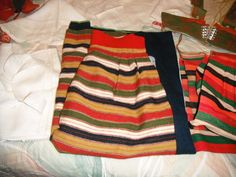 Vintage authentic Swedish girl's costume purchased in Sweden at least 60 years ago. (See photograph showing a twelve year old girl wearing it.) Pieces include the skirt in vibrant colors, apron panel, white button front blouse with red embroidery on sleeve cuffs, vest with original cording, scarf, white cap, black hat with pompoms at end of red streamer, red handbag, cumberbund in green/gold, and long red stockings. Handmade in Sweden.