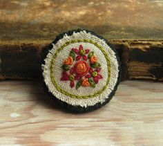 Orange Roses Embroidered Brooch Hand embroidered orange rose bouquet stitched on natural linen and backed with dark green felted wool. Size: just