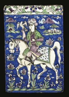 A QAJAR MOULDED TILE, IRAN, 19TH CENTURY   Of rectangular form, painted under a clear glaze with cobalt blue, green and manganese, featuring a rider in green robes, a falcon on his right wrist, leading a white horse across a landscape, the raised upper band decorated with birds on scrolling flowers - 9½ x 14¼in (24.1 x 36.1cm)