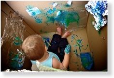 Paint inside a cardboard box. Genius: they get as messy as they want, but the house does NOT.  Definately doing this with my kids :)