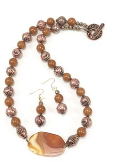 Attention-grabbing necklace of molded gold beads with pumpkin-colored glass beads culminating in a faceted glass accent bead. $18.