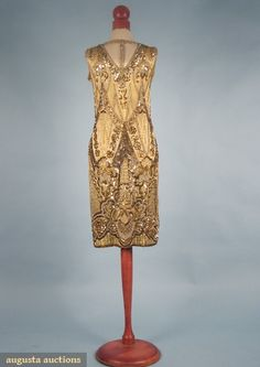 "NINA RICCI BEADED DRESS, MID 1920s    Gold silk satin w/ diamante, gold & silver sequins & gold bugle beads in allover zigzag & striped design w/ large florals, B 34"", H 36"", L 39"", (right shoulder has 1"" tear & some weakness to fabric, some bead loss, green discoloration to silk in midriff area) fair."