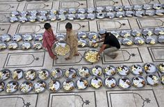 Volunteers prepare plates for Iftar (breaking fast after sunset) during the holy month of Ramadan at a mosque in Karachi, Pakistan