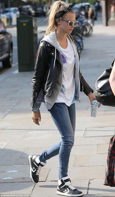 Cara rocking a weekend look with a leather jacket and Nike high tops.
