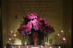 Para la entrada una combinación de 3 copas con flores en tonos morados/rosas