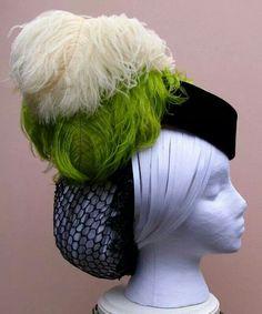 Cappello semplice in velluto blu impreziosito tuttavia da piume e dotato di una retina per raccogliere i capelli. Costo £80
