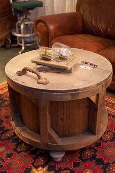 This old cheese mold, found at an antiques sale, has been repurposed into a coffee table. The handle opens an interior that makes for a great storage space.