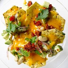 POWER NACHOS! You've got everything you need to make em: Olive oil, cannellini beans, cilantro, lime juice, celery, red onion, tortilla chips, reduced-fat cheddar cheese, #avocado, salsa | health.com