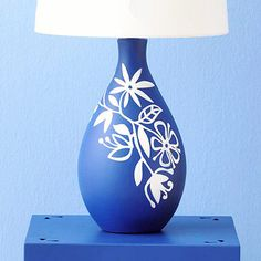 Flower Mask ~~  Made of flexible plastic, a mask is opposite of a stencil and is easily applied to the base. Attach the mask to the lamp, then spray-paint the entire base. Remove the mask, immediately after spraying, to reveal the graphic design.