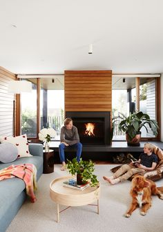 Bright living room with central fireplace set in a timber feature wall in modernist home in Melbourne's inner south-east. Photography: Annette O'Brien | Stylist: Becky Littler | Story: Australian House & Garden