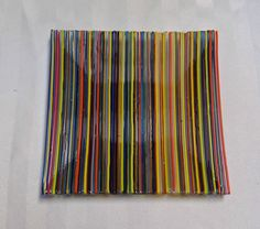 """Fused Glass Handmade Decorative Plate - Colorful Rods on Clear Base. This small plate can be used as a display piece or to hold trinkets, coins, whatever you wish. It measures 6"""" square and is 1/4"""" high. I created this plate by very carefully gluing multiple colors of 1 and 2mm glass stringers (rods) to a clear 6"""" base, making sure to line the edges up. Then I fused the plate to 1400 degrees F so that the rods are permanently melted into the clear base but still retain the rounded…"""