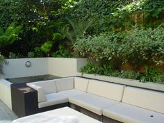 contemporary all weather rattan wicker woven lounge furniture with raised white rendered planter walls and water feature