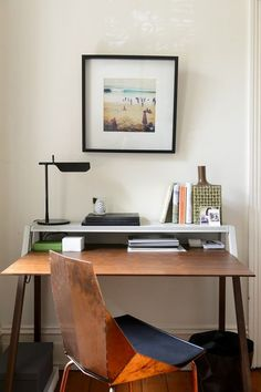 The FLOS Tab table lamp adds a modern touch to this wood desk area with a unique seat and framed photography as wall art.