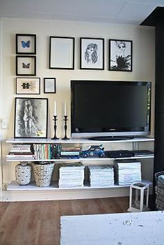 Tv wall with pipe shelves. Art. Mags. Sans candles.. In the closet... Like a hidden entertainment center