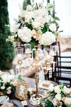 Glamorous vintage candlestick centerpiece with flowers | Image by Nate + Lori