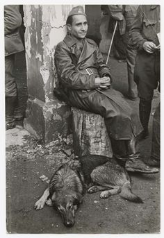 Robert Capa, [Sitting volunteer and dog, farewell ceremony for the International Brigades, Les Masies, Spain], October 25, 1938