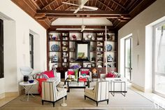 The Cartagena, Colombia, property of interior designer Richard Mishaan dates from the 16th century. In the living area, a vintage measuring stick leans against shelving arrayed with decorative objects.   archdigest.com