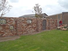 Versierde tuinmuur met steunbeertjes, oude stalramen; kinderraam; boog voor dubbele deur.