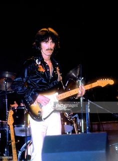 Former Beatle George Harrison (1943-2001) plays his guitar during the Dark Horse Tour circa 1972 at the Cow Palace in Daly City, California.