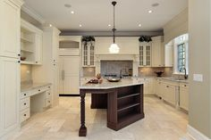 Crisp, white and light gray kitchen with dark middle island. Includes white cabinets, display cabinets and kitchen desk area.