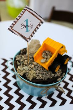 Neat centerpiece idea for construction theme party. I'd use a galvanized bucket, add soil, gravel, and a cheap toy. Will hold the tablecloth down, too!