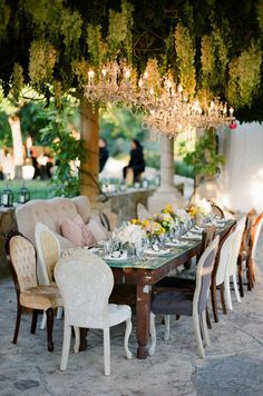 A live ceiling covered in greenery is brought to life with bright crystal chandeliers.