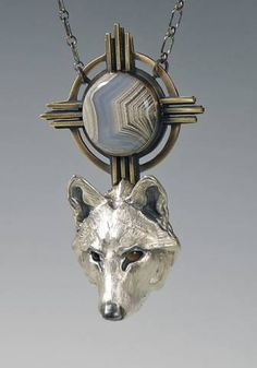White Wolf under Winter Sun by Brooke Stone Jewelry Handcrafted Cast and fabricated sterling silver, fabricated bronze, Mexican Laguna Agate, Smoky Quartz eyes, sterling silver chain.   Wolf head: 1 1/2 inch length. Overall length: 3 inches.