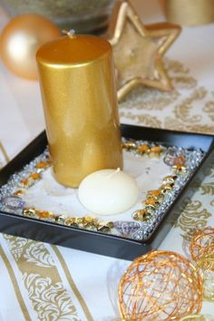 A simple way to make a beatiful centerpiece is to work with sands in which we place the candle, and some gold decoration.