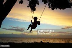 ストックフォト : Silhouette of child on swing at sunset.